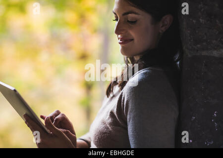 Young woman leaning against wall using touchscreen on digital tablet - Stock Photo