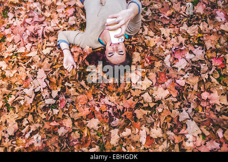 Overhead view of young woman lying on autumn leaves taking selfie on smartphone - Stock Photo