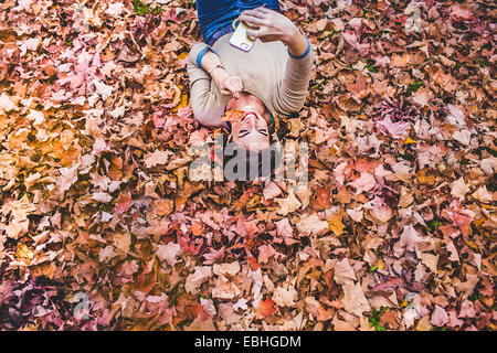 Overhead view of young woman lying on autumn leaves taking smartphone selfie - Stock Photo