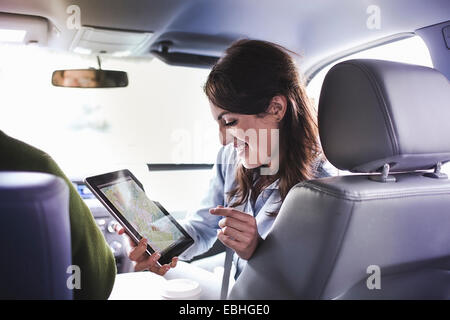 Over shoulder view of young woman in car front seat using digital tablet map - Stock Photo