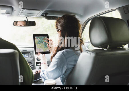 Over shoulder view of young woman in car front seat using digital tablet touchscreen map - Stock Photo