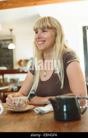 Mid adult woman drinking tea in country store cafe - Stock Photo