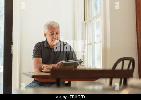 Mature man using digital tablet in country store cafe - Stock Photo