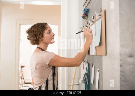 Female shop assistant writing on wall clipboards in kitchen at country store - Stock Photo