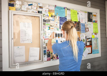 Mid adult woman photographing community notice board with smartphone - Stock Photo