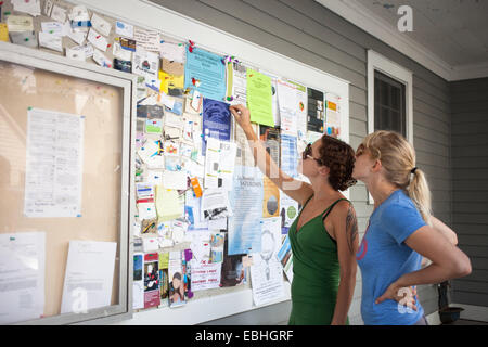 Two mid adult women looking up at community notice board - Stock Photo