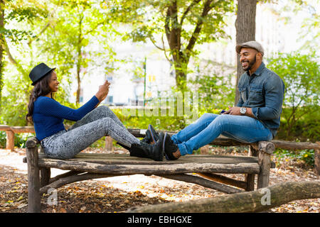 Couple taking photograph on bench, Central Park, New York, USA - Stock Photo