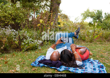 Couple lying on grass watching movie on tablet - Stock Photo