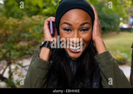 Young woman smiling and holding smartphone to ear - Stock Photo