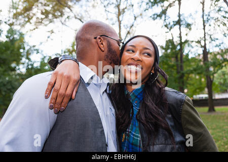 Man kissing woman's cheek in park - Stock Photo