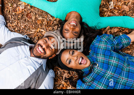 Friends lying on fallen autumn leaves - Stock Photo