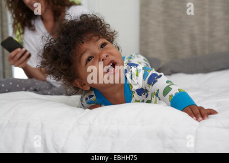 Male toddler crawling on bed whilst mother using smartphone - Stock Photo