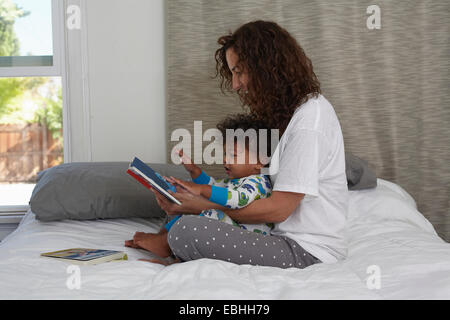 Young woman sitting on bed reading book to toddler son - Stock Photo
