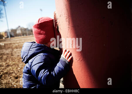 Male toddler playing hide and seek in park - Stock Photo