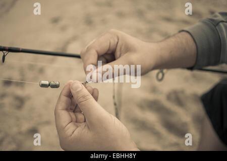 Close up of fishermans hands preparing fishing rod, Truro, Massachusetts, Cape Cod, USA - Stock Photo