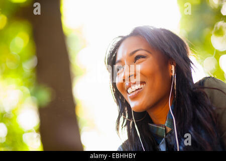 Young woman with wide smile in park - Stock Photo
