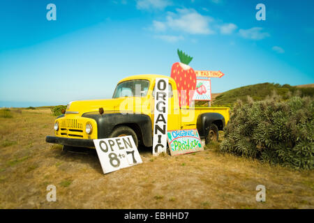 Yellow pickup truck and strawberry jam advertisement on roadside, Big Sur, Davenport, California, USA - Stock Photo
