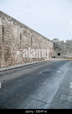 View of historic stone Land Gate wall as it runs along 18th Street  including empty street and clear blue sky Campeche, - Stock Photo