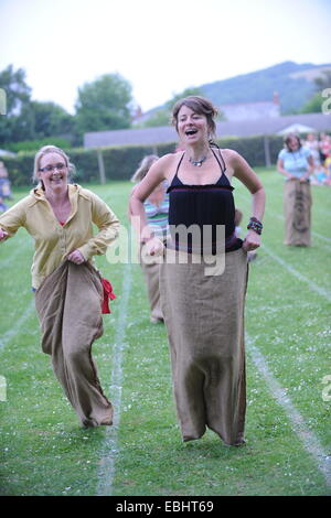 Mums in a sack race at a school sports day - Stock Photo