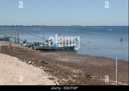 Two fishermen standing in one of several beached panga boats with long bamboo fishing poles along the Guf of Mexico - Stock Photo