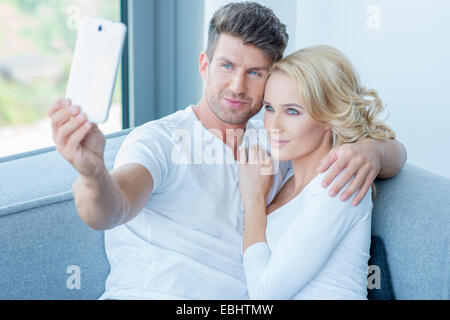 Close up Smiling Young Sweet Lovers in White Shirts Taking Self Photos While Sitting on the Gray Couch. - Stock Photo