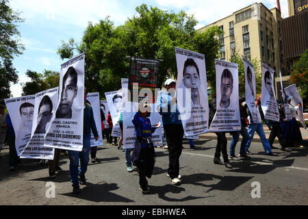 Protesters carry banners with faces of the 43 missing students in Mexico during a march to demand their release, - Stock Photo