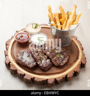 Portion of BBQ beef filet mignon steak  served  on wooden board with  ketchup, mustard and cream sauces, fried potatoes - Stock Photo