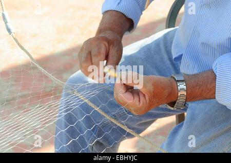 Italy, Liguria, Laigueglia, Fisherman Mending his Nets - Stock Photo