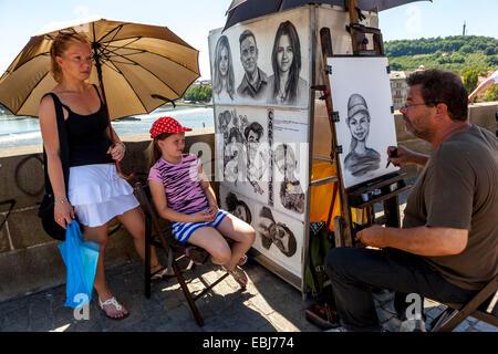 Street artist at work on Charles Bridge in Prague, Czech Republic - Stock Photo