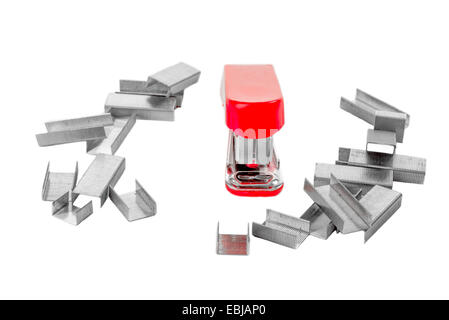 Little red stapler on white isolated background, facing the viewer, and surrounded by staples. - Stock Photo