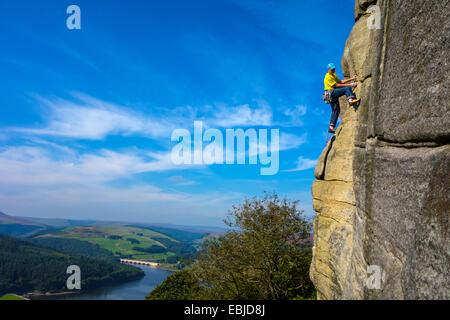 Rock climber in yellow on Bamford Edge, Derbyshire, Peak District, with Ladybower Reservoir behind - Stock Photo