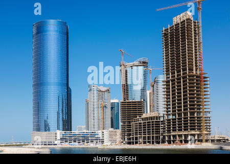 Modern high-rise residential and office buildings under construction at City of Lights on Al Reem Island in Abu - Stock Photo