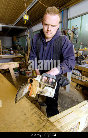 carpenter working with chain saw - Stock Photo