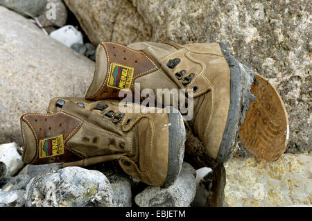 worn out walking boots among boulders, Germany - Stock Photo