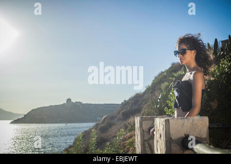 Young woman looking at view of the sea - Stock Photo