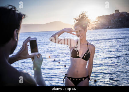Man photographing young woman on vacation - Stock Photo