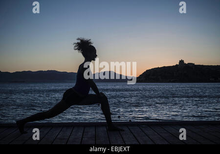Young woman doing yoga by sea, silhouette - Stock Photo