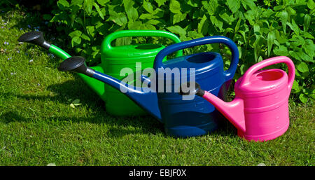three plastic watering cans standing side by side on a garden lawn, Germany - Stock Photo