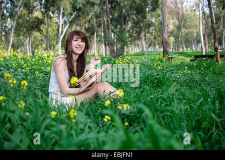 Young woman sitting in forest, reading book - Stock Photo