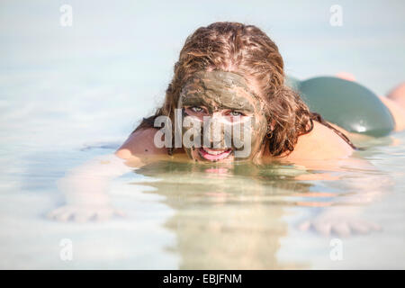 Mud covered female tourist floats in the Dead Sea, Israel - Stock Photo