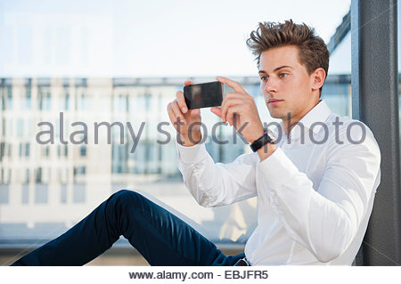 Young businessman using smartphone - Stock Photo