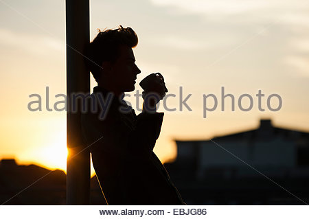 Young man leaning against post, drinking coffee, sunset - Stock Photo
