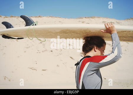 Surfer carrying surfboard on head at beach, Lacanau, France - Stock Photo