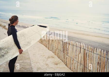 Surfer with surfboard on beach, Lacanau, France - Stock Photo