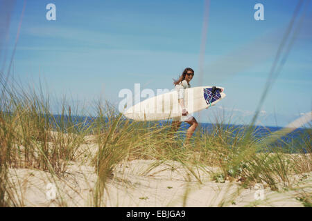 Woman with surfboard on beach, Lacanau, France - Stock Photo