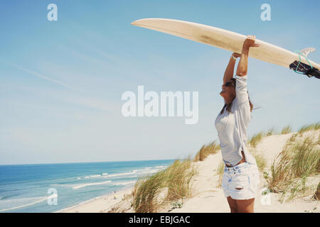 Woman with surfboard on beach, Lacanau, France - Stock Photo