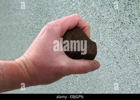 hand with a stone in front of a broken pane of security glass - Stock Photo