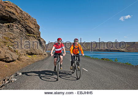Cyclists cycling on road next to Kleifarvatn, Reykjanes, South West Iceland - Stock Photo