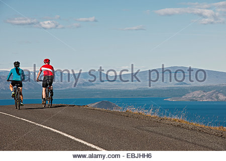 Cyclists on road next to Thingvallavatn, Langjokull in background, Thingvellir National Park, South West Iceland - Stock Photo