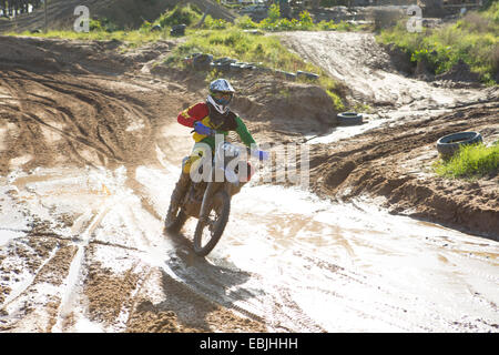 Young male motocross rider racing on muddy track - Stock Photo